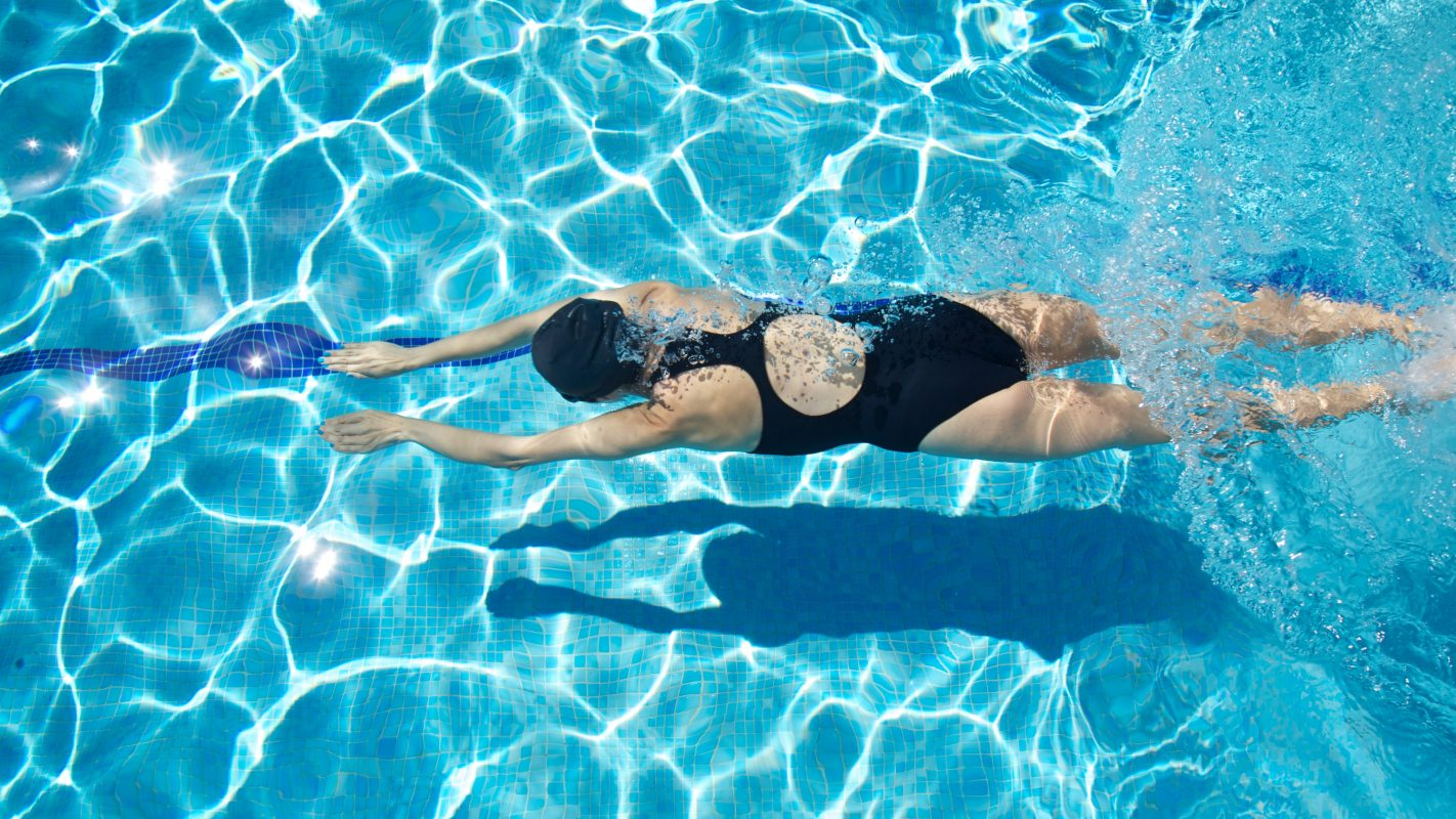 sport woman with black swimsuit and cap swimming and diving in a blue reflecting water pool
